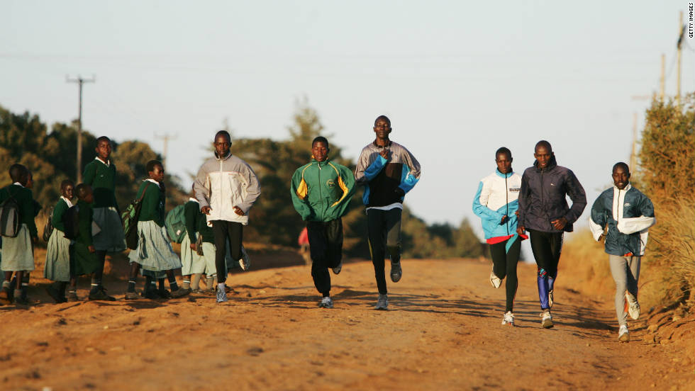Young athletes from the Kip Keino High Performance Training Centre run past schoolchildren in Eldoret, Kenya.