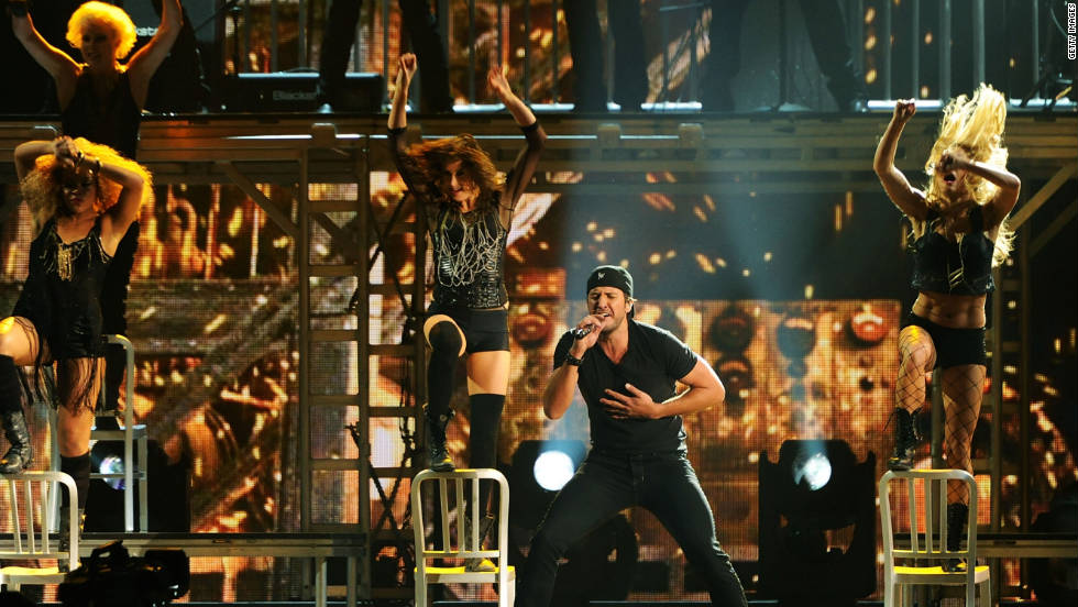 "Luke Bryan pumps up the crowd with a few scantily clad dancers and his single ""Country Girl (Shake It for Me)."""