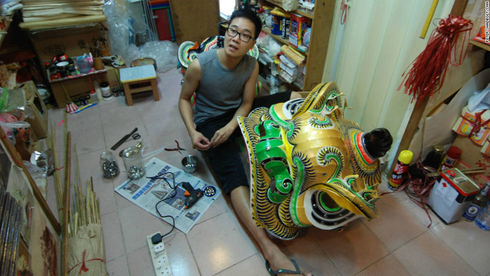 Yu puts the finishing touches on a Lion Dance mask in his funeral goods shop