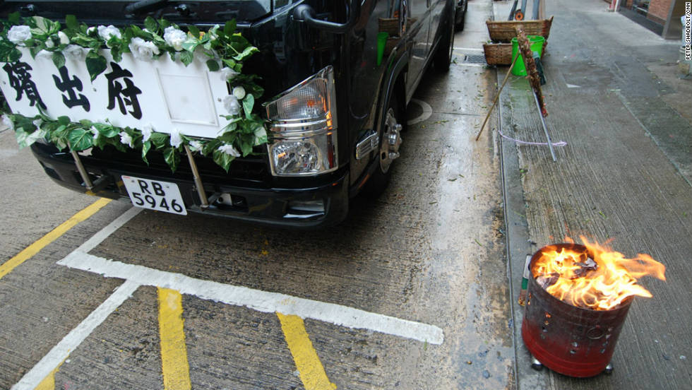 Offerings are burnt in a brazier on a street in Hung Hom next to a funeral van
