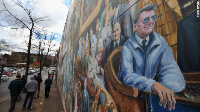 "In State College, people walk by ""Inspiration,"" a mural that depicts Joe Paterno, fired over the sex assault case of Jerry Sandusky."