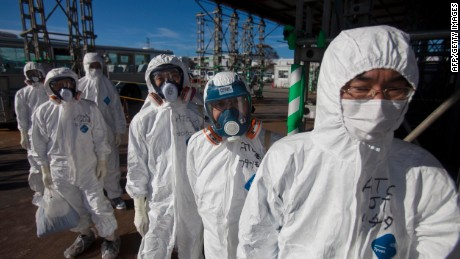 Workers in protective suits and masks wait to enter the emergency operation center at the crippled Fukushima Dai-ichi nuclear power station in Okuma on November 12, 2011.