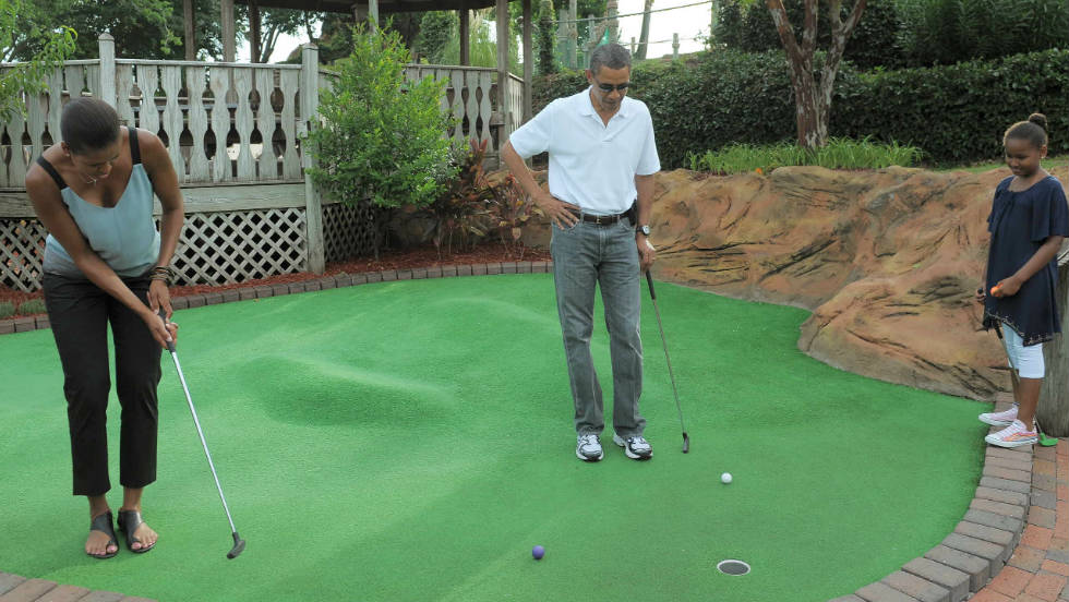 U.S. President Barack Obama and daughter Sasha watch as First Lady Michelle Obama putts on the first hole during a round of mini golf in Florida in 2010.