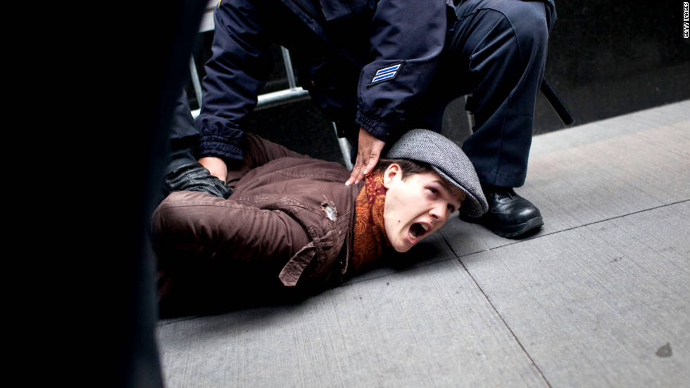 Police oficers arrest a protester in the Financial District. Scores were arrested Thursday in New York.