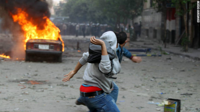 Egyptian protesters throw stones during clashes with security forces on Monday in Cairo's Tahrir Square.