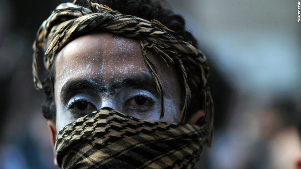 A protester, his face sprayed with protective medical cream, covers his nose and mouth to avoid tear gas inhalation at Cairo's Tahrir Square on November 22, 2011.