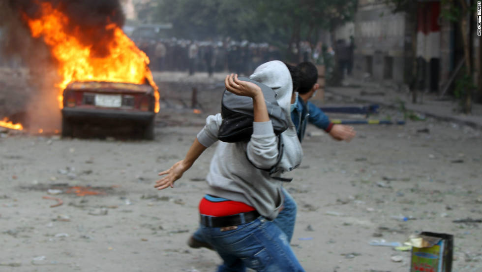 Eyptian protesters throw stones during clashes with security forces at Tahrir Square in Cairo on November 21, 2011.