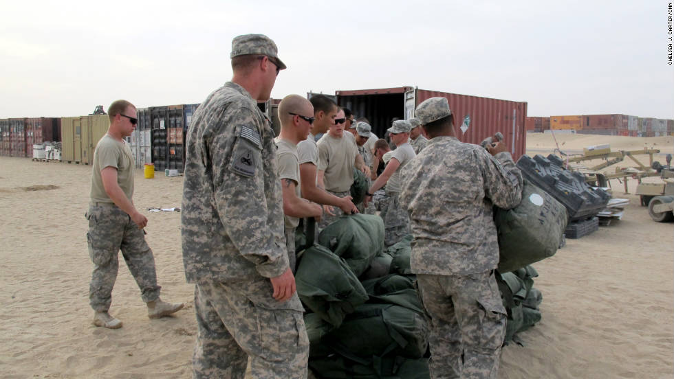 Soldiers load their duffle bags onto a shipping container in Kuwait. The road home for most troops requires them to cross from Iraq into Kuwait, where they turn in equipment before starting the journey back to the United States.