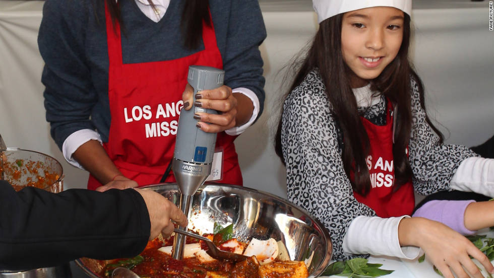 Zoe Saldana serves Thanksgiving meals to the homeless at a charity event in Los Angeles.