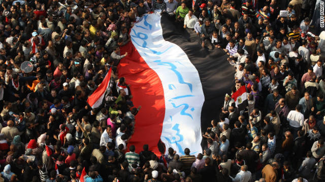 CAIRO, EGYPT - NOVEMBER 25: Protestors carry a giant Egyptian flag in Tahrir Square during a mass rally on November 25, 2011 in Cairo, Egypt. Thousands of Egyptians are continuing to occupy Tahrir Square ahead of parliamentary elections to be held on November 28, 2011. (Photo by Peter Macdiarmid/Getty Images)