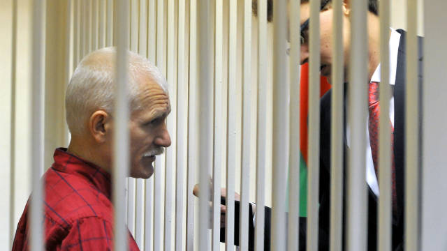 The head of Viasna Human Rights Center, Ales Bialiatski, speaks with his lawyer from the defendant's cage in a court in Minsk, on November 24, 2011.