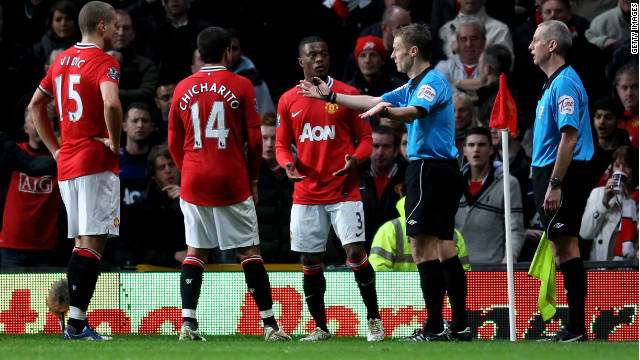 Ref Michael Jones gestures to the Manchester United players after consulting with his assistant and awarding a penalty.