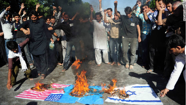 Demonstrators burn U.S., NATO and Israeli flags during a religious procession in Karachi, Pakistan, on Monday.
