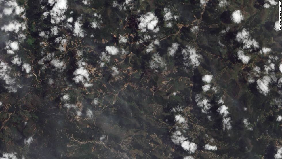 "The tiny streaks of brown in this NASA image are in many instances giant <a href=""http://edition.cnn.com/2011/WORLD/americas/01/18/brazil.flooding/index.html"">landslides</a> which resulted from flash floods in mountainous terrain 60 kilometers north of Rio de Janeiro in January. They caused at least 900 deaths making it one of the worst natural disasters in Brazil's history, according to the World Meteorological Organization (WMO)."