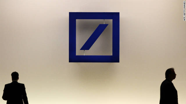 People walk by the logo of German company Deutsche Bank.