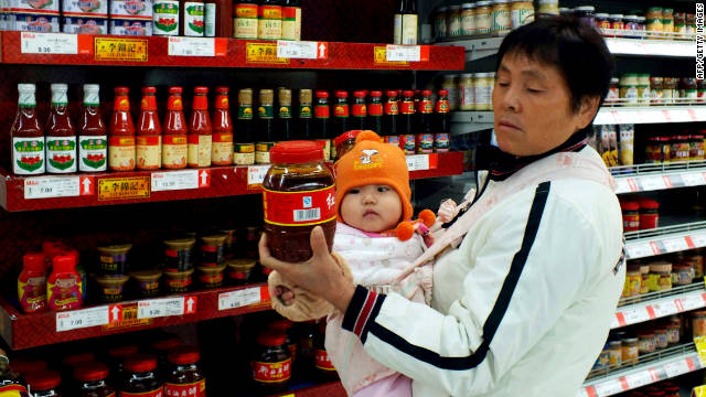 A Chinese woman inspects a bottle of chilli sauce at a supermarket in Yichang, central China's Hubei province on November 9, 2011.