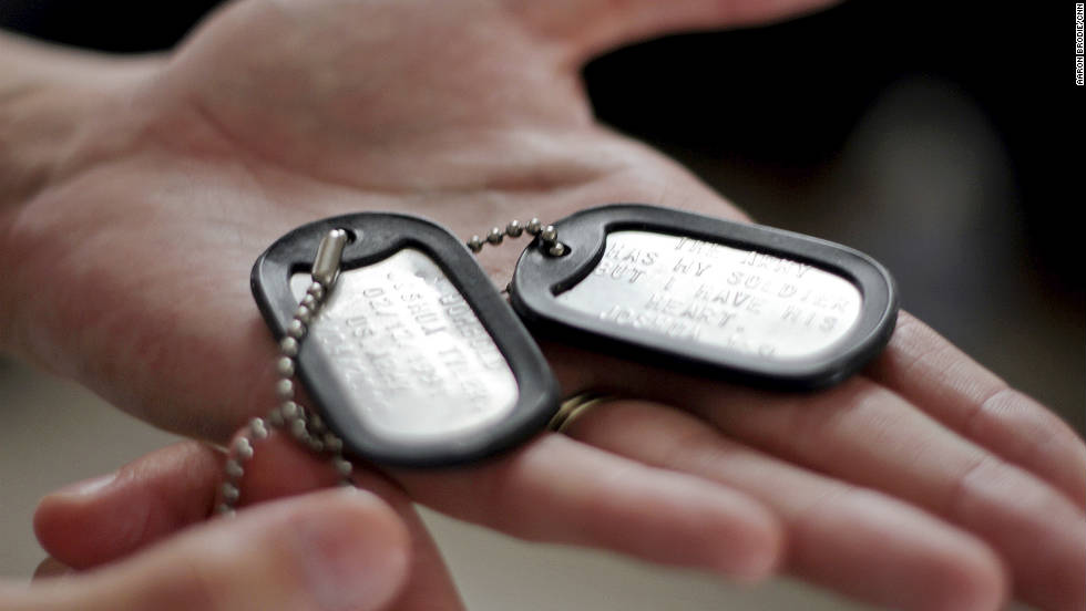 "Sarah Wombold holds a dog tag that reads, ""The Army has my soldier but I have his heart."" Her husband, Pfc.  Josh Wombold, was deployed to Iraq during the summer of 2011 while she was pregnant with their first child."