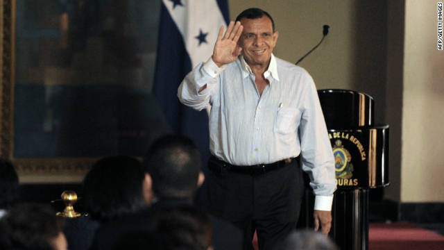 Honduran President Porfirio Lobo waves to the members of his cabinet, before a national broadcast in Tegucigalpa, on June 1, 2011.