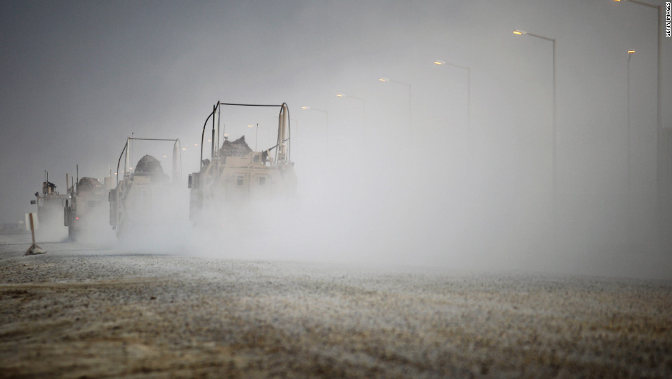 U.S. Mine Resistant Ambush Protected (MRAP) vehicles drive through Camp Adder before departing what is now known as Imam Ali Base on December 16.