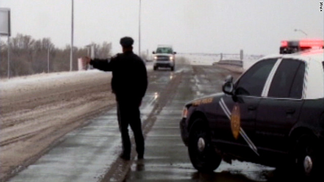 A cop directs highway traffic in New Mexico on Monday. Parts of the Southwest could see up to 2 feet of snow.