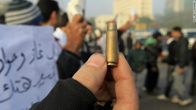 A protester holds up a bullet casing after deadly clashes with the military in Tahrir Sqaure