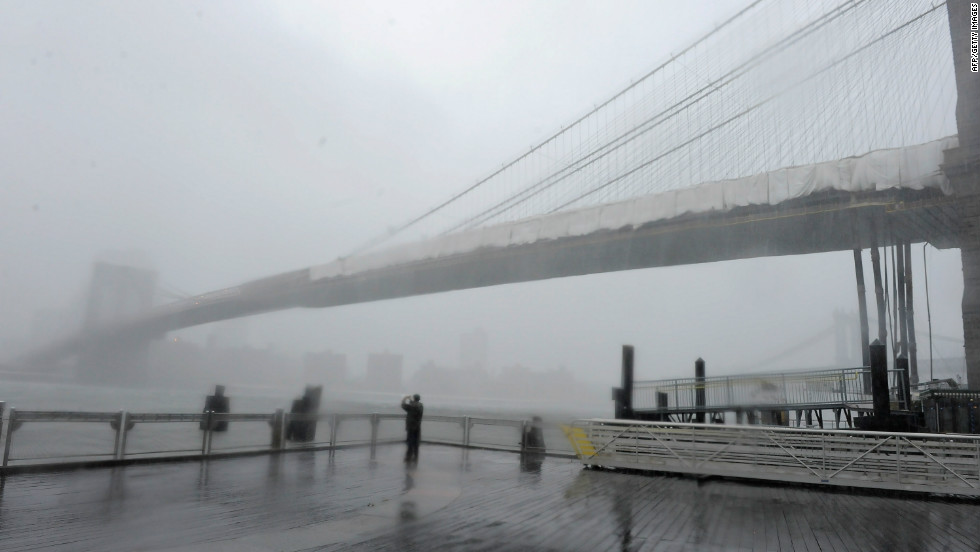 "Brooklyn Bridge stands shrouded in heavy rain and dark clouds as Hurricane Irene reaches the New York City area on August 28, 2011. According to Jan Corfee-Morlot, senior climate change analyst for the OECD, many developed coastal cities around the world face a ""severe risk"" of floods in the coming years."