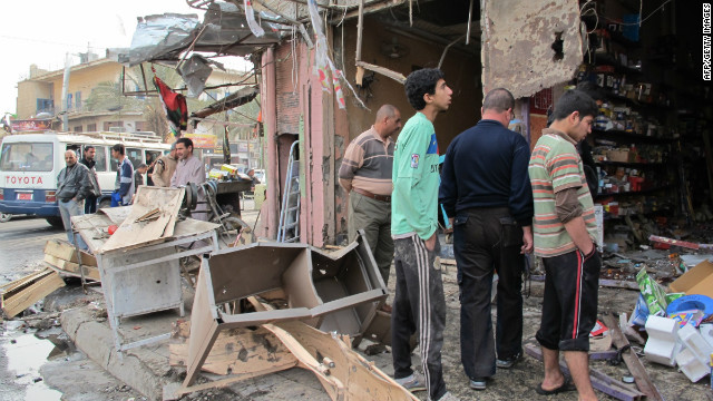 Iraqis inspect damage after a wave of attacks in Baghdad killed dozens of people on December 22.