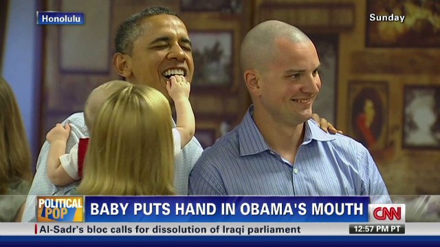 nr baby puts hand in obama mouth_00002328