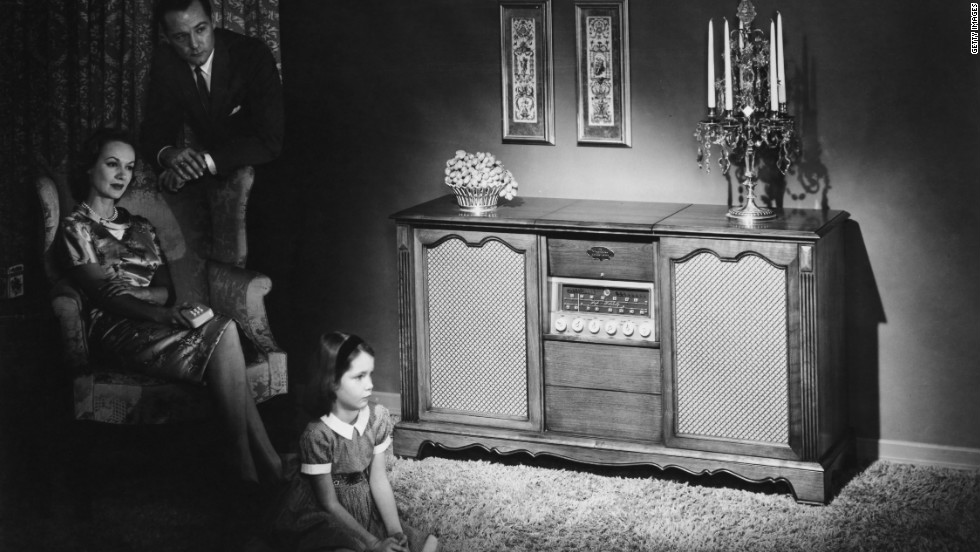 "A family listens to a Magnavox Concert Grand radio in their home. Hit radio programs ""Suspense"" and ""Yours Truly, Johnny Dollar"" aired the last broadcasts in 1962. Many would say this ended the ""Golden Age of Radio."""