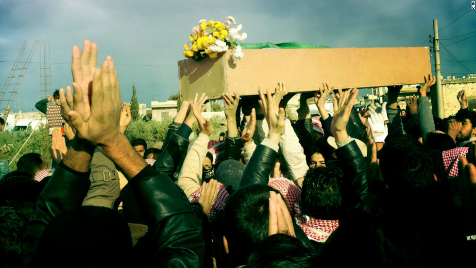 "Mourners raise their hands at the funeral procession for ""Malik,"" who was shot by government forces in Dar al-Kabira in Homs."