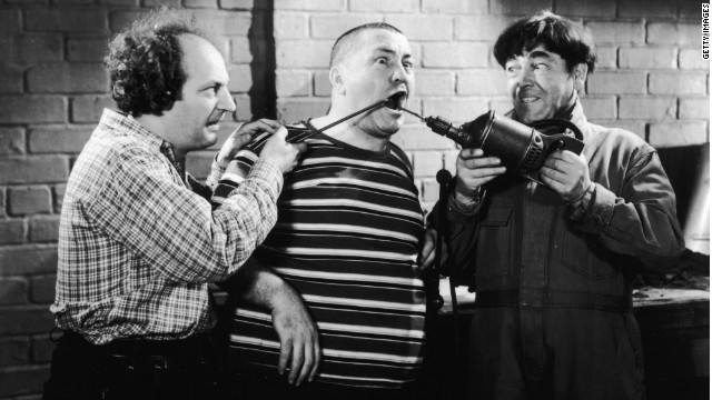 Larry Fine and Moe Howard practice their form of dentistry on Curly Howard in a still from a Three Stooges film.