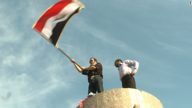 Dhirgham al-Zaidi, right, stands atop a pedestal that once held Saddam Hussein's statue as the Iraq flag is waved on Friday.