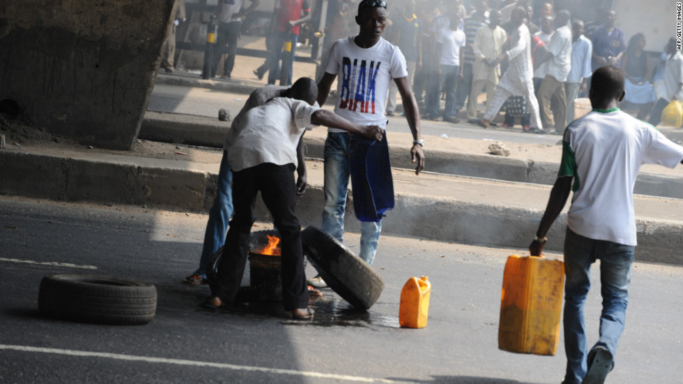 Bystanders watch as protestors try to set fire to a car tire in the middle of Ikorodu Road in Lagos.