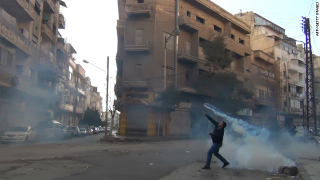 A protester in the flashpoint Syrian city of Homs throws a tear gas bomb back toward security forces last week.