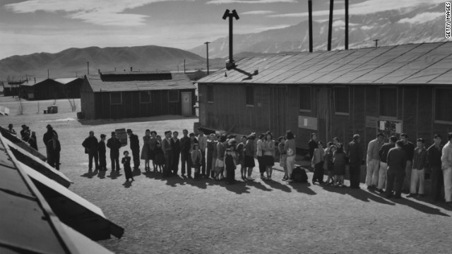 People wait in a line in front of a building at midday at a Japanese internment camp in 1943.