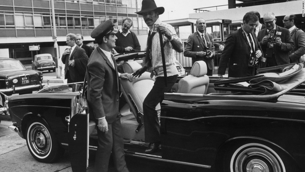 No better way to arrive: Actor, singer, dancer, Sammy Davis Jnr takes delivery of a black Rolls-Royce convertible at London Airport in 1969.