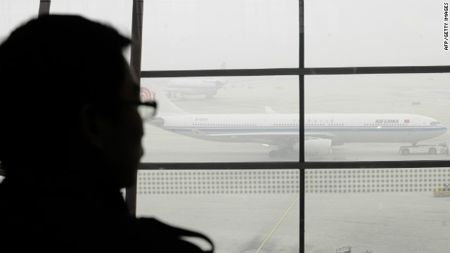 A traveller looks out at an airplane shrouded in smog at Beijing International Airport on December 5, 2011.