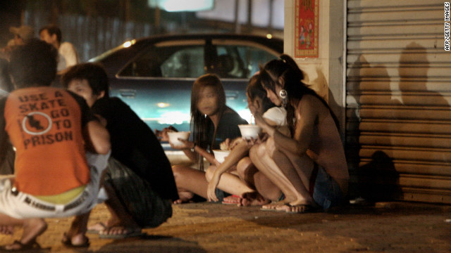 Cambodian sex workers sit on the side walk along a street in Phnom Penh on December 18, 2008.