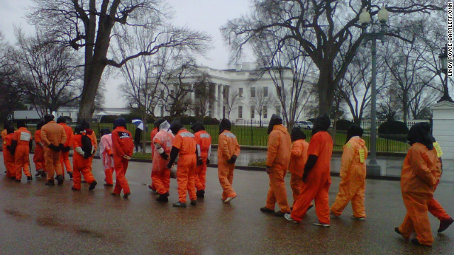 Protesters in orange jumpsuits symbolizing Guantanamo Bay detainee uniforms march past the White House on Wednesday.