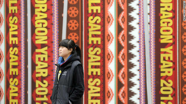 A woman passes a sale advertisment on a shop in Shanghai on January 9, 2012.