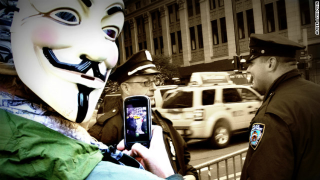 A member of Anonymous keeps an eye on NYPD officers during a recent Occupy Wall Street protest.