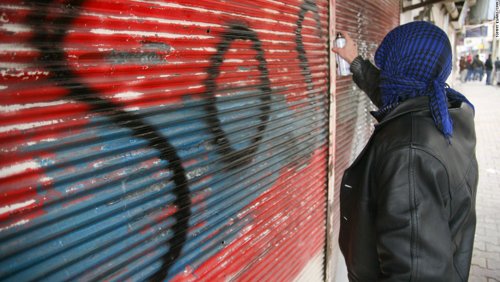 A protester spray paints S.O.S on the front of a shop that has been shut down.