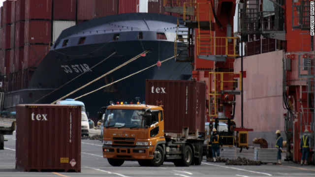 Containers are loaded and unloaded from a container vessel at a Tokyo port in this 2011 file photo.