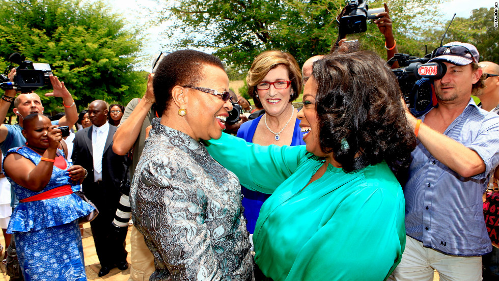 Winfrey greets Graca Machel, the wife of former South African president Nelson Mandela, on her arrival at the inaugural graduation of the class of 2011.