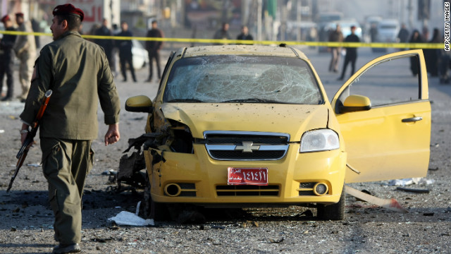 An Iraqi soldier inspects the site of a blast after a bomb ripped through a group of workers in Sadr City in Baghdad on January 24, 2012.