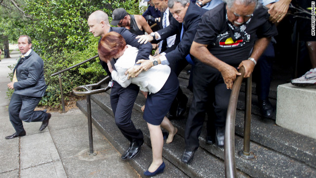 Australian Prime Minister Julia Gillard (C, white jacket) is bundled out of a restaurant by security service agents after it was surrounded by furious Aboriginal rights protesters in Canberra on January 26, 2012.   Gillard and opposition leader Tony Abbott were stranded in The Lobby restaurant as dozens of demonstrators from a protest against Australia Day, which marks the arrival of British settlers in 1788, converged on the hotel.    AUSTRALIA OUT  - NO ARCHIVES - NO INTERNET - RESTRICTED TO SUBSCRIPTION USE - RESTRICTED TO EDITORIAL USE  AFP PHOTO / AAP / Lukas Coch (Photo credit should read LUKAS COCH/AFP/Getty Images)
