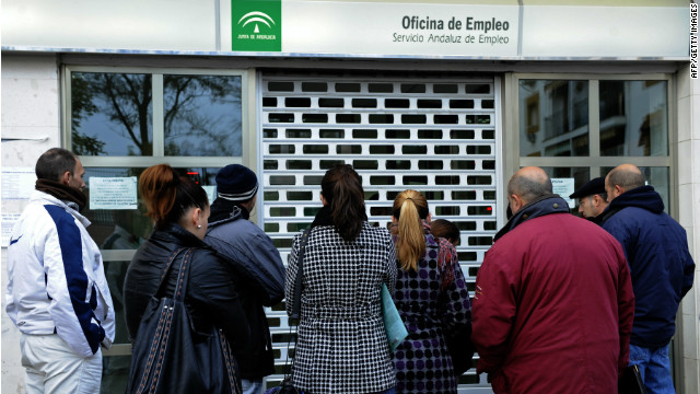 People wait in line in front of a government employment office in Sevilla, Spain, on Friday.