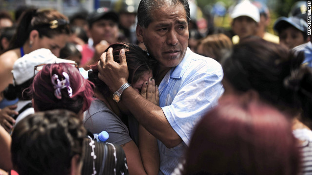 Relatives grieve for a victim of a fire at a rehabilitation clinic in Lima, Peru, on Saturday.