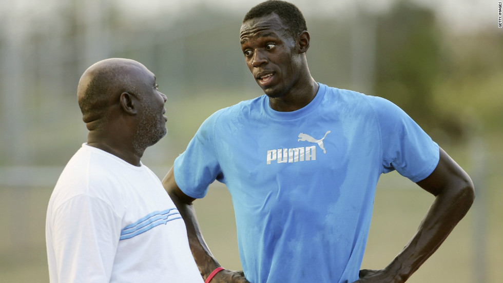 Jamaican sprinter Usain Bolt (right) speaks with coach Glen Mills during a training session in Kingston.