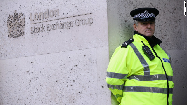 A police officer stands guard in front of the London Stock Exchange, October 17, 2011.
